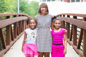 Black family, mother and two daughters, standing on a bridge